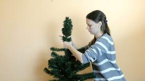 妇女连接分支到人为树的上面 在圣诞节以后整理 股票视频