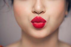 妇女送与明亮的红色唇膏的` s嘴唇一个飞吻 免版税库存照片