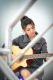 妇女选址和使用吉他 免版税图库摄影