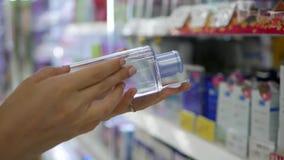 妇女选择和买液体构成去膜剂的` s手 妇女选择面孔关心和化妆用品的化妆水 影视素材