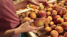 妇女选择在商店柜台的桃子 她在一个塑料盒投入桃子 股票视频