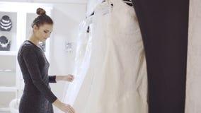 妇女选择婚礼服在新娘精品店 股票录像