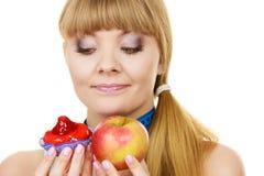 妇女选择果子的或蛋糕做出饮食选择 免版税库存照片
