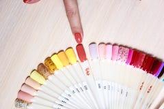 妇女选择波兰语的颜色修指甲的 钉子的设计 测试器指甲油 时尚修指甲 图库摄影