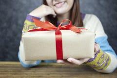 妇女选择聚焦递拿着有红色丝带的礼物盒 免版税库存图片