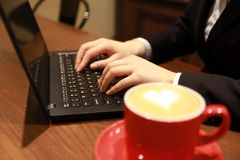 妇女递与在咖啡店的一台膝上型计算机一起使用 库存照片