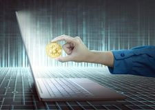 妇女递与拿着金黄bitcoin的膝上型计算机 库存图片