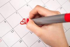 妇女递与铅笔图在日历的心脏形状为情人节 免版税库存照片