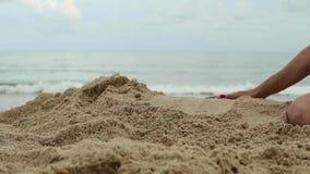 妇女递使用与沙子在异乎寻常的海滩和被弄脏的海洋背景 暑假概念 股票录像