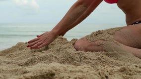 妇女递使用与沙子在异乎寻常的海滩和被弄脏的海洋背景 暑假概念 影视素材