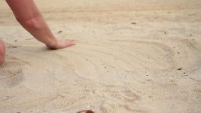 妇女递使用与沙子在异乎寻常的海滩和被弄脏的海洋背景 暑假概念 股票视频