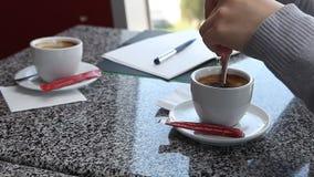 妇女递加糖入在咖啡馆的咖啡 股票视频