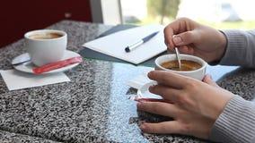 妇女递加糖入在咖啡馆的咖啡 影视素材