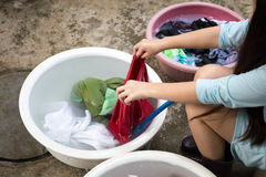 妇女递在一个大碗的洗涤的肮脏的衣裳 库存图片