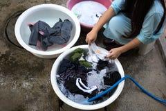妇女递在一个大碗的洗涤的肮脏的衣裳 库存照片