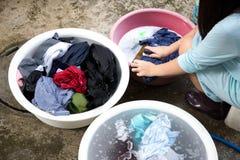 妇女递在木板的洗涤的肮脏的衣裳有衣裳的b 库存照片