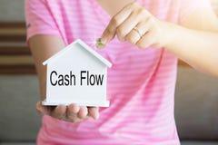 妇女递投入金钱硬币在存钱罐和现金流动词,攒钱概念 免版税库存照片