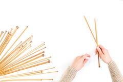 妇女递拿着一个对木编织针 在白色背景的许多另外大小竹编织针 免版税库存照片