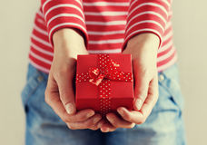 妇女递拿着一个礼物或当前箱子有红色丝带弓的  免版税库存照片