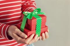 妇女递拿着一个礼物或当前箱子有绿色丝带弓的  图库摄影