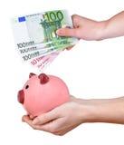 妇女递拿着一张桃红色存钱罐和欧洲钞票 库存照片