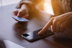 妇女递拿着信用卡和使用smarth电话 付出 免版税库存图片