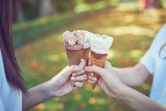 妇女递拿着冰淇凌碰撞和愉快 弛豫时间 免版税库存照片