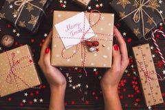 妇女递拿着圣诞节有明信片快活的xmas的节日礼物箱子在装饰的欢乐桌上 免版税库存图片