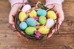 妇女递拿着在一张小巢被定调子的图片的被绘的复活节彩蛋 顶视图 选择聚焦 库存图片