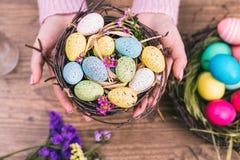 妇女递拿着在一张小巢被定调子的图片的被绘的复活节彩蛋 顶视图 选择聚焦 图库摄影