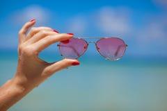 妇女递拿着在热带海滩的太阳镜 免版税库存图片