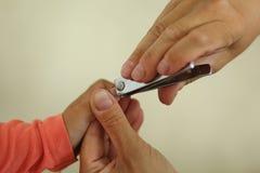 妇女递拿着手切开有飞剪机的小孩指甲盖的孩子 免版税图库摄影