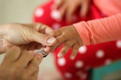 妇女递拿着手切开有飞剪机的小孩指甲盖的孩子 免版税库存照片