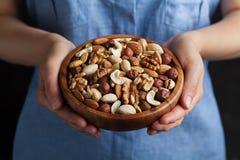 妇女递拿着有混杂的坚果的一个木碗 健康食物和快餐 核桃、开心果、杏仁、榛子和腰果 免版税库存图片