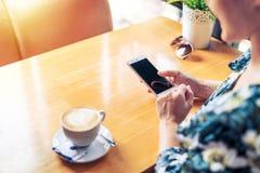 妇女递拿着有空白的拷贝空间屏幕正文消息内容的,女性手机在手机的读的新闻在咖啡店 免版税图库摄影