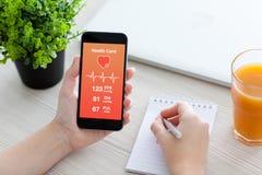 妇女递拿着有app的电话保健卡监视的 免版税库存照片