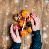 妇女递拿着柑橘圣诞节玩具蜜桔圣诞节棒棒糖木背景顶视图舱内甲板位置被定调子的雪 免版税图库摄影