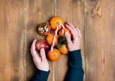 妇女递拿着柑橘圣诞节玩具蜜桔圣诞节棒棒糖木背景顶视图舱内甲板位置 免版税库存照片
