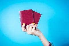 妇女递持两本护照反对蓝色背景 库存照片