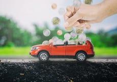 妇女递放硬币入一辆红色汽车填满 买新的汽车的挽救的概念 库存图片