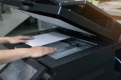 妇女递放纸片入一个复制的设备 图库摄影