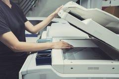 妇女递放纸片入一个复制的设备 免版税图库摄影