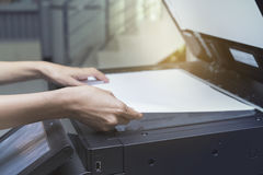 妇女递放纸片入一个复制的设备 库存照片