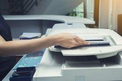 妇女递放纸片入一个复制的设备 免版税库存照片