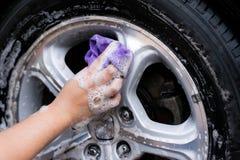 妇女递有布料和油漆的洗涤的汽车与玻璃抹服务 库存照片