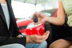妇女递汽车关键字给一个人在汽车经销商 免版税库存照片