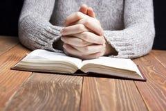 妇女递祈祷与在黑暗的一部圣经在木桌 免版税库存图片