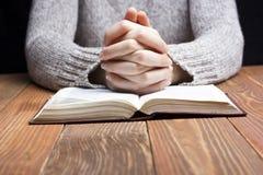妇女递祈祷与在黑暗的一部圣经 免版税库存图片