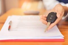 妇女递给汽车遥远的钥匙,在签字的合同约定和成功的成交后 库存图片