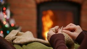 妇女递编织的羊毛袜子在坐由火的圣诞节时间 股票录像